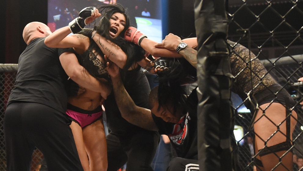 LAS VEGAS, NV - AUGUST 08:  Fighter Shelly 'Aphrodite' DaSilva (2nd L) is restrained by coach Michael Modest (L) and assistan