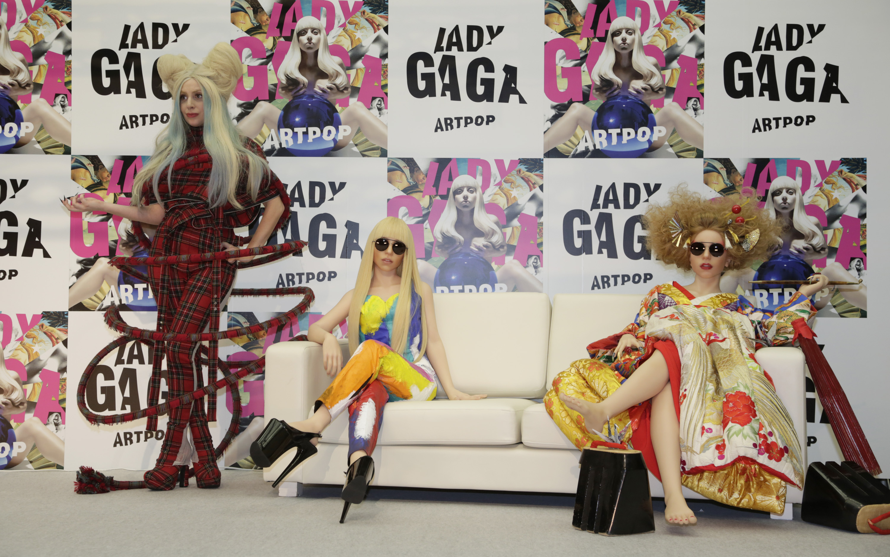 Lady Gaga poses for photographers with her life-sized dolls during a press conference to promote her album 'ARTPOP' in Tokyo,