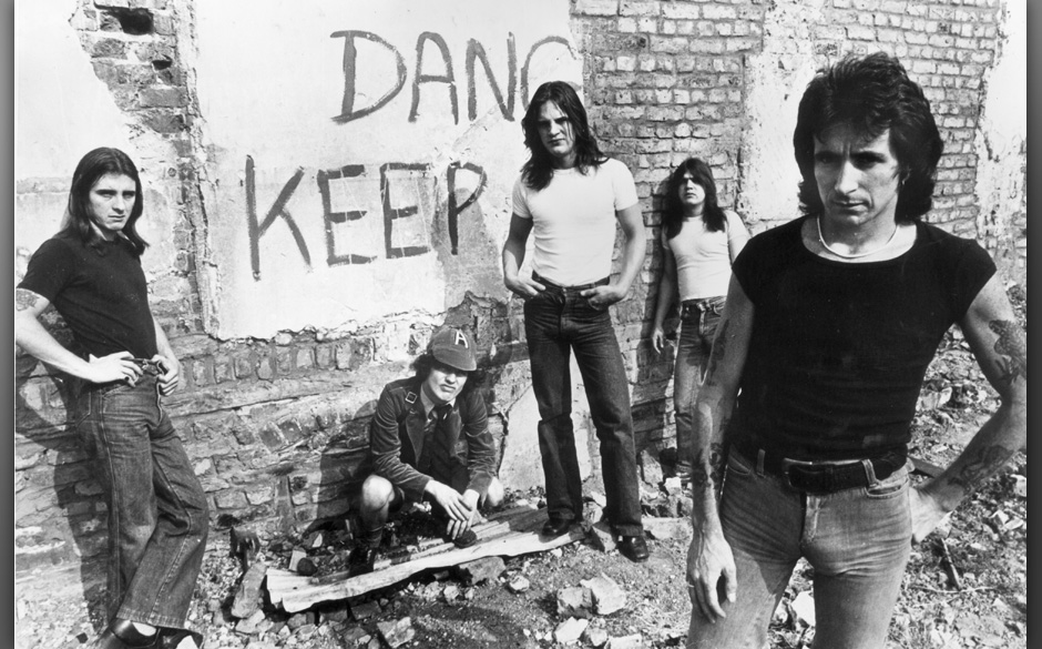 1977:  Promotional portrait of Australian hard-rock group AC/DC standing in front of a graffiti-covered brick wall, (L-R:) dr