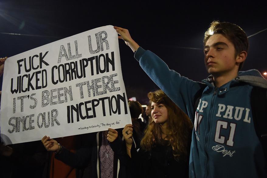 Rumänische Bürger protestieren gegen ihre Regierung. Das Plakat zeig einen Songtext der Band Goodbye To Gravity, während deren Konzert das Feuer ausbrach.