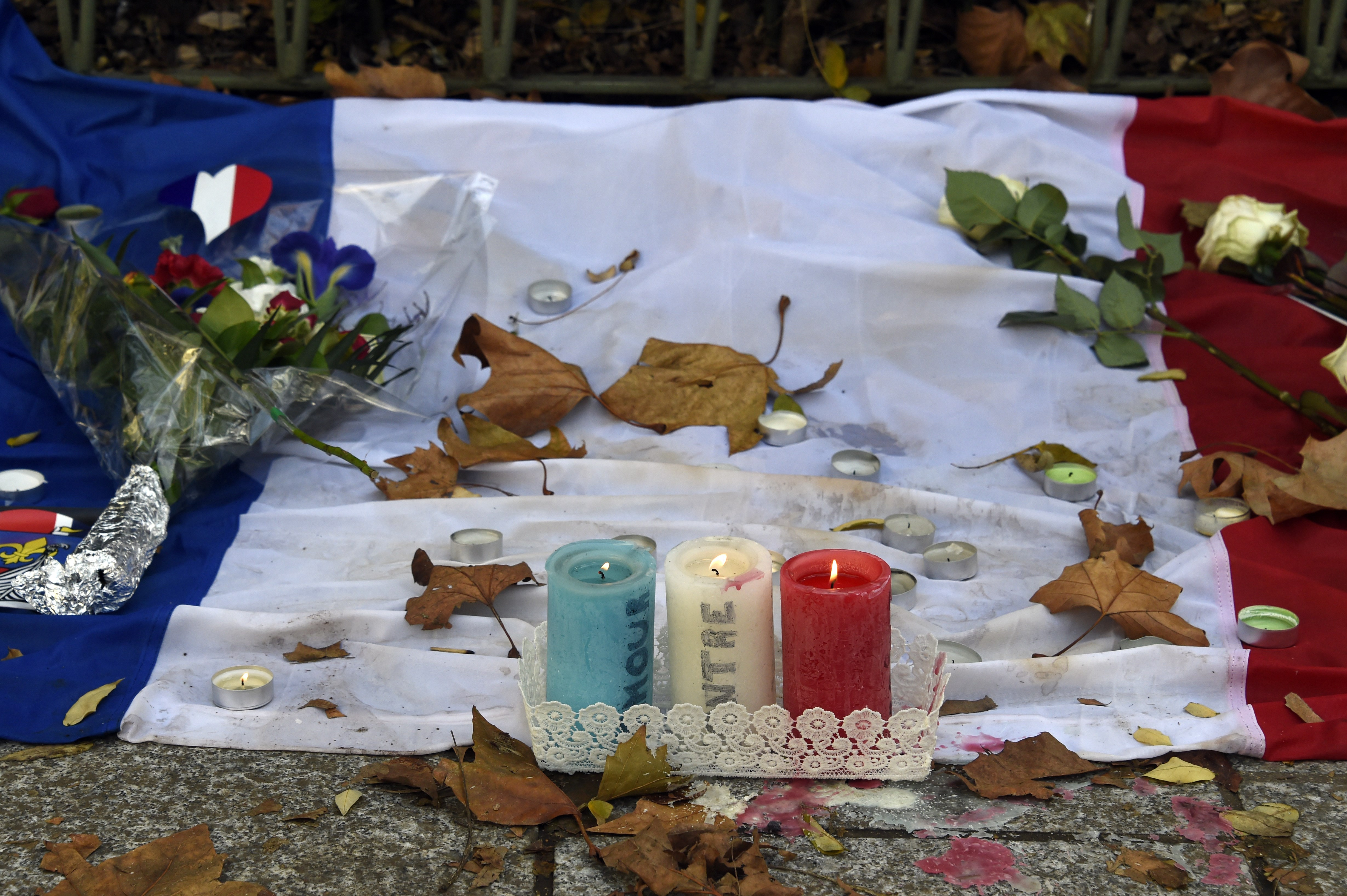 Candles bearing the colours of the French flag burn at a makeshift memorial for the victims of the attacks, on November 18, 2