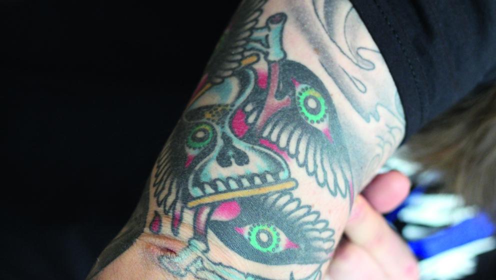 Den Mittelpunkt des Tattoos bilden zwei Sensen und einen Sanduhr. Wie bei den meisten Tattoos des Kvelertak-Sängers hat auch