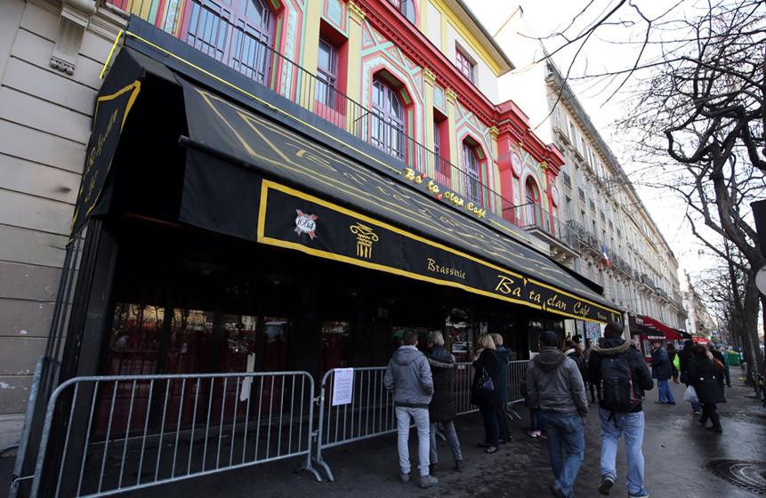People stand in front of the Bataclan concert hall in Paris on December 22, 2015, after the sidewalk in front of the venue wa