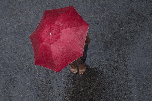 TOPSHOT - A woman shelters under an umbrella under heavy rain and strong wind in Rio de Janeiro, Brazil, on February 29, 2016