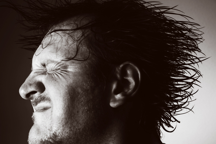 Close-up of man with wet hair in motion.