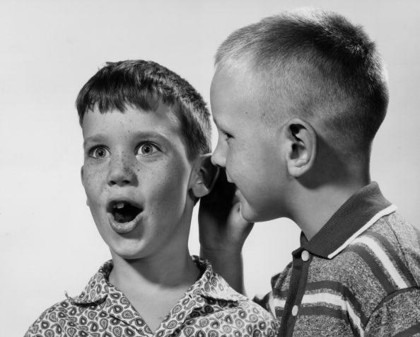 circa 1955:  Studio headshot of one young boy whispering a secret in another boy's ear, who looks surprised. There is a white