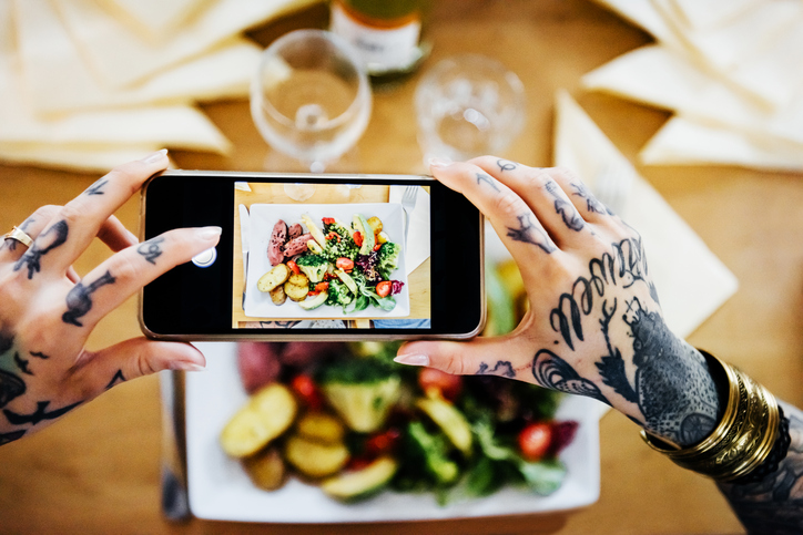 Overhead shot of tattooed hands of a young woman taking pictures of her dinner plate