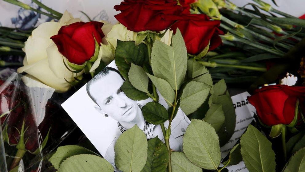 A picture taken on July 22, 2017 shows red roses and a picture of  Linkin Park frontman Chester Bennington laid in front of t