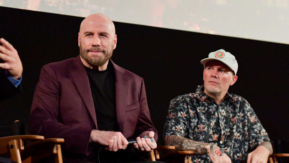 HOLLYWOOD, CALIFORNIA - AUGUST 22: John Travolta and Fred Durst speak onstage during the premiere of Quiver Distribution's 'T