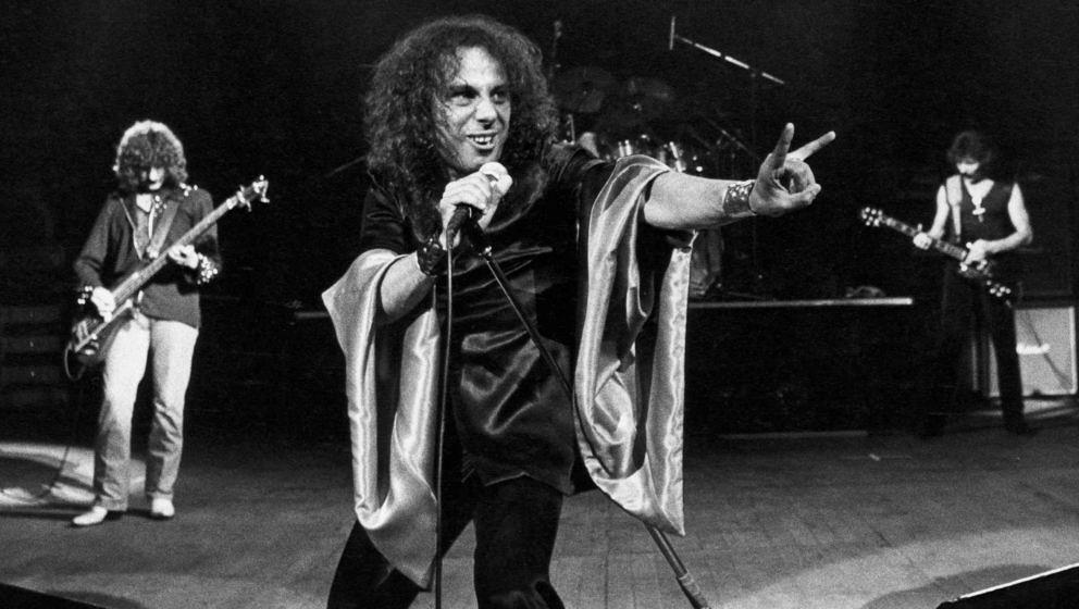 Ronnie James Dio macht zwischen Geezer Butler (l.) und Tony Iommi seine berühmten Teufelshörner