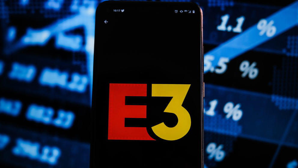 POLAND - 2021/06/15: In this photo illustration an E3 logo displayed on a smartphone with stock market percentages on the bac