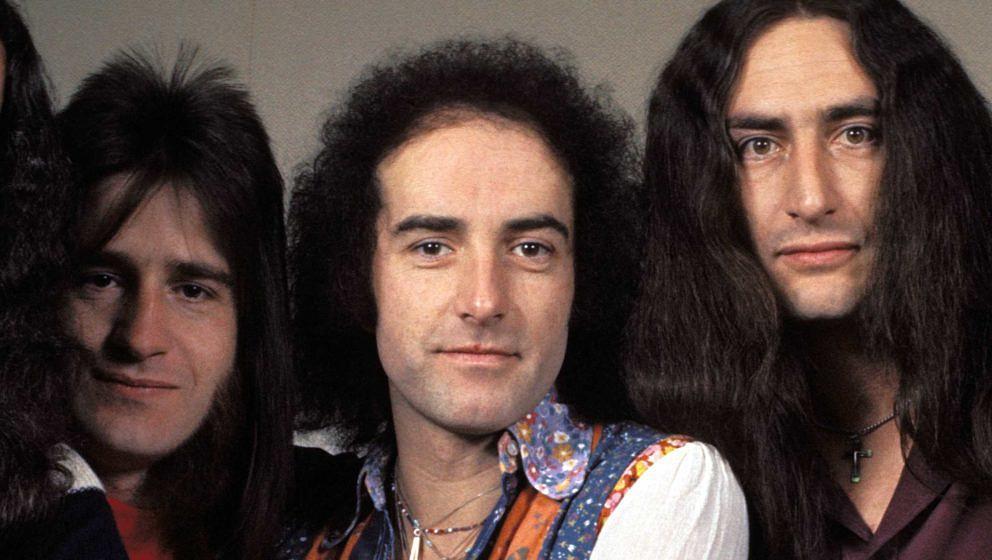 Trevor Bolder (l.) und Ken Hensley von Uriah Heep nehmen John Lawton in die Mitte