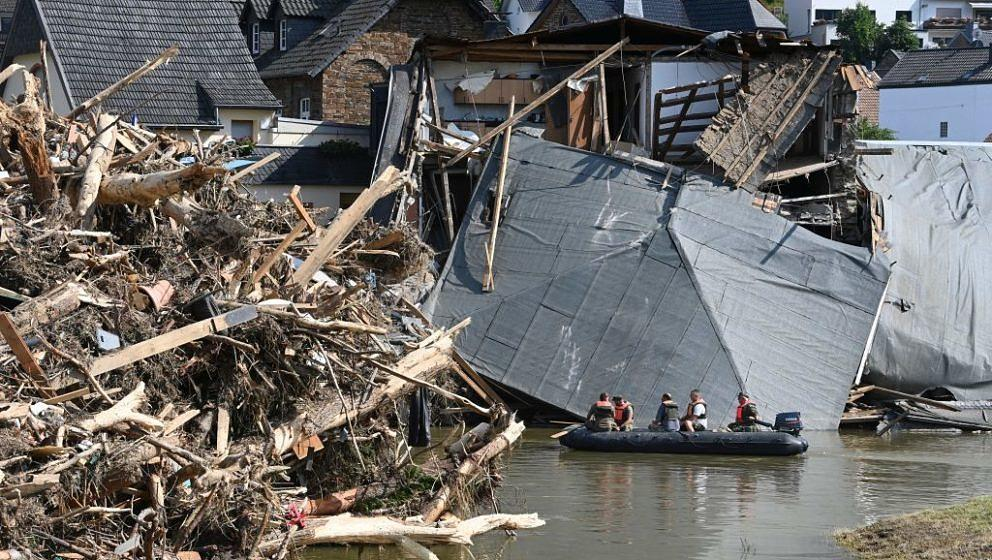 Military personnel floats on a boat on the Ahr river as the roof of a damaged house hangs on the water and uprooted trees are